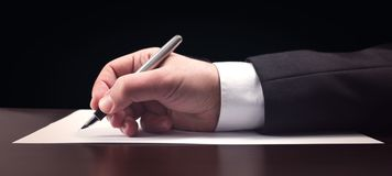 Writing Official Document. Businessman Writing Or Signing An Official Document Stock Photos