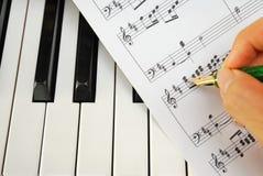 Writing On Music Score With Pen On Piano Keyboard Stock Photo