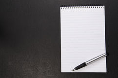 Writing pad and pen. On a black leather texture Stock Image
