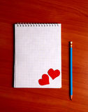 Writing Pad on the Table. Blank Writing Pad with Heart Shapes and Pencil On The Table Royalty Free Stock Image