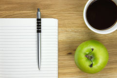 Writing paper and ballpoint-pen on wooden desk. Writing paper and ballpoint-pen, green apple and coffee mug on wooden desk Royalty Free Stock Image