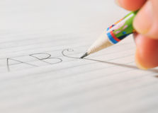 Writing on a Paper by a pencil. Kids first alphabet writing on a Paper by a pencil Royalty Free Stock Image