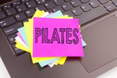 Writing Pilates text made in the office close-up on laptop computer keyboard. Business concept for Fitness Balance Workout Exercis. E Workshop on the black Stock Photos