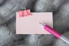 Writing pink pen on light pink sticker with pink metal clamp stationery royalty free stock photography