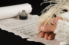 Writing a poem. Handwriting a poem on old paper scroll Royalty Free Stock Images