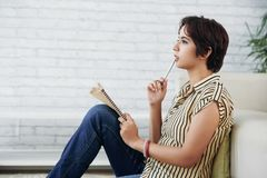 Writing poem. Thoughtful pretty young Indian woman writing poem stock photo