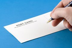 Writing a Postcard. Person writing the address on a postcard Royalty Free Stock Image