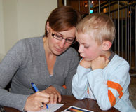Writing Postcards. Six year old boy watching his mother writing postcards sitting at a wooden table Stock Photography