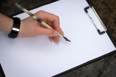 Writing with a quill. Drawing beginning, a feather on a clean sheet Stock Photo