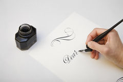 Writing with quill pen. Spilled ink and fountain pen concept image for writing process. Vintage nib pen and inkwell Royalty Free Stock Photo