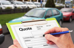 Writing a Quote for Car Repair. Hand with pen writing a quote or estimate for car repairs Royalty Free Stock Photo