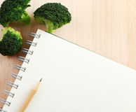 Writing a Recipe. Directly above close-up view of a table with a broccoli and a notebook on cutting board Stock Image