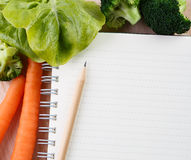 Writing a Recipe. Directly above close-up view of a table with a carrots, broccoli, green salad  and a notebook on cutting board Stock Photos