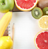 Writing a Recipe. Directly above close-up view of a table with a notebook and tropical fruit Stock Images
