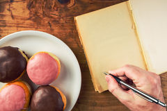 Writing recipe for homemade delicious doughnuts with sweet toppi Stock Photography