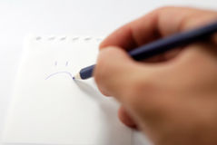 Writing a sad smiley on a note paper. Writing a smiley, close-up Royalty Free Stock Photos