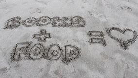 Writing in the sand about books and food. Statement of likes in the sand Royalty Free Stock Photos