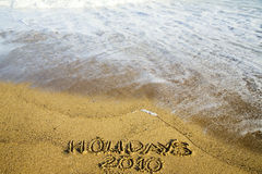 Writing on sand about holidays 2010 Royalty Free Stock Image