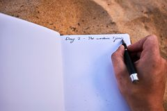 Human hand holding a pen and writing notes in a travel journal diary in the sand on white paper. The writing says Day 2 - The western Fjords. It is written on Royalty Free Stock Photography