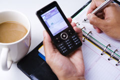 Writing schedule on organizer from phone cell stock photography