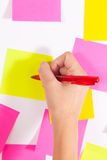 Writing on screen- Wall covered with sticky notes Stock Photo