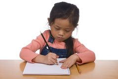 Writing Series 4. A young girl erases a mistake in her writing Stock Image