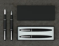 Writing set. Ball pen and ink pen with a box on a concrete backg. 3d render writing set with a stylish box. Ball pen and ink pen on a concrete background. Top Royalty Free Stock Images