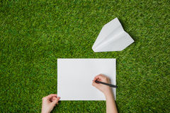 Writing on sheet of paper with airplane nearby Royalty Free Stock Photo