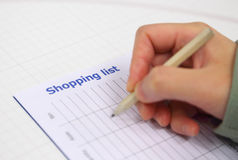 Writing shopping list for xmas season Royalty Free Stock Images
