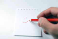 Writing a smiley on a note paper. Writing a smiley, close-up Royalty Free Stock Image