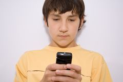 Writing sms. Boy writes the message on the cell telephone royalty free stock photo