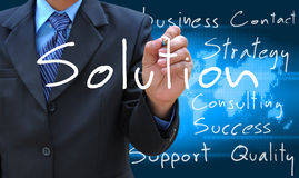 Writing solution. A businessman hand writing solution Stock Photography