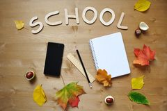 School autumn background. Writing supplies, mobile phone, autumn leaves over wooden desk background, school time concept, copy space Royalty Free Stock Photos