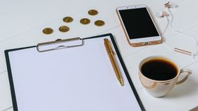 Writing tablet with paper, pen, coffee, smartphone and coins on white table. Royalty Free Stock Images