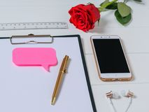 Writing tablet with paper, pen, headphones, pencil and rose on white table. Stock Photography