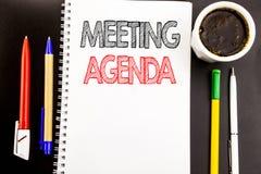 Writing tekst pokazuje spotkanie agendę Biznesowy pojęcie dla Biznesowego rozkładu planu Pisać na notepad nutowego papieru tle z  Zdjęcia Stock