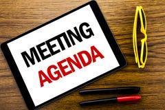 Writing tekst pokazuje spotkanie agendę Biznesowy pojęcie dla Biznesowego rozkładu planu Pisać na pastylka laptopie, drewniany tł Zdjęcia Stock