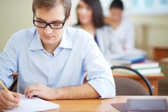 Writing test. Portrait of group of students making notes or writing test with serious guy in front Royalty Free Stock Photos