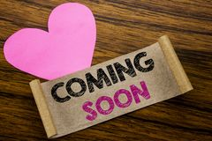 Writing text showing Coming Soon. Business concept for Message Future written on sticky note paper, wooden wood background. With p Stock Photo