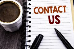 Writing text showing Contact Us. Business concept for Customer Support written on notebook book note paper on the wooden wood back. Writing text showing Contact stock image