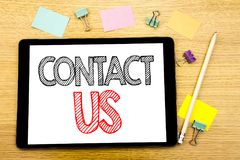 Writing text showing Contact Us. Business concept for Customer Support Written on tablet laptop, wooden background with sticky not. Writing text showing Contact royalty free stock image