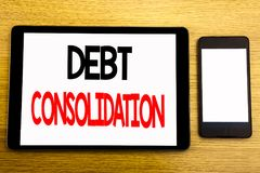 Writing text showing Debt Consolidation. Business concept for Money Loan Credit Written on tablet laptop, wooden background with s. Writing text showing Debt Stock Photo