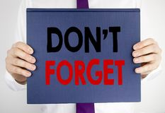 Writing text showing Do Not Forget. Business concept for Don t memory Remider written on book notebook paper holding by the man in. Writing text showing Do Not Stock Images