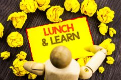 Writing text showing  Lunch And Learn. Business photo showcasing Presentation Training Board Course written on Sticky Note Holding Royalty Free Stock Images