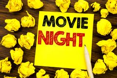 Writing text showing Movie Night. Business concept for Wathing Movies Written on sticky note paper, wooden background with folded. Writing text showing Movie stock image