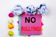 Writing text showing No Bullying written on sticky note in office with screw paper balls. Business concept for Bullies Prevention Stock Images