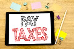 Writing text showing Pay Taxes. Business concept for Taxation Overtax Return Written on tablet laptop, wooden background with stic. Writing text showing Pay Royalty Free Stock Images