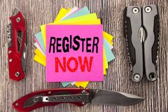 Writing text showing Register Now. Business concept for Registration For Written on sticky note wooden background with pocket knif. Writing text showing Register Royalty Free Stock Image