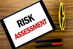 Writing text showing Risk Assessment. Business concept for Safety Danger Analyze Written on tablet laptop, wooden background with. Writing text showing Risk royalty free stock photo