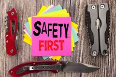 Writing text showing Safety First. Business concept for Safe Warning Written on sticky note wooden background with pocket knife. Writing text showing Safety Stock Image